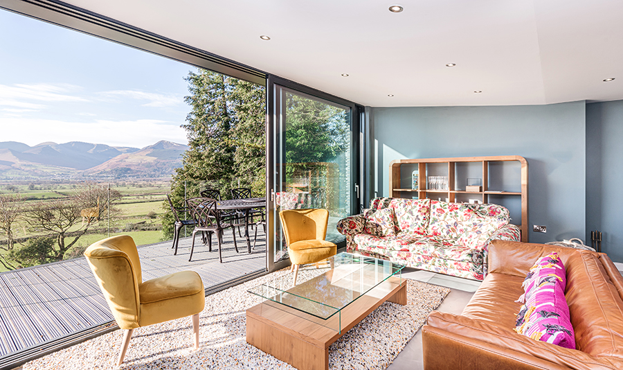 open plan living room with glazed sliding doors opening on terrace with glass balustrade Lake District