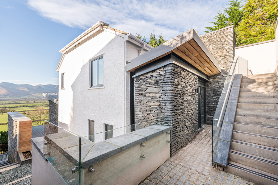 Stone clad entrance porch with timber soffit glass balustrade stepped access granite setts Lake District