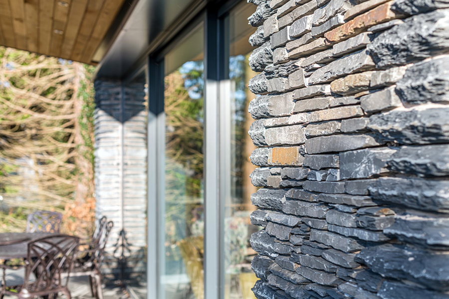 Stone clad extension with aluminium sliding doors Lake District