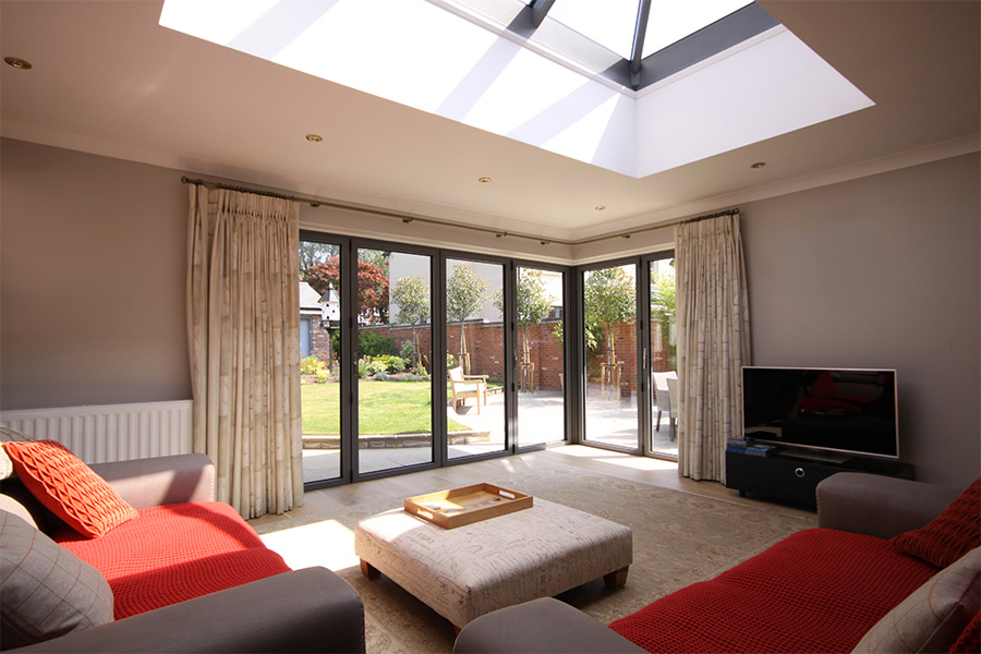 large roof lantern over open plan living in garage conversion wth sliding doors opening onto garden