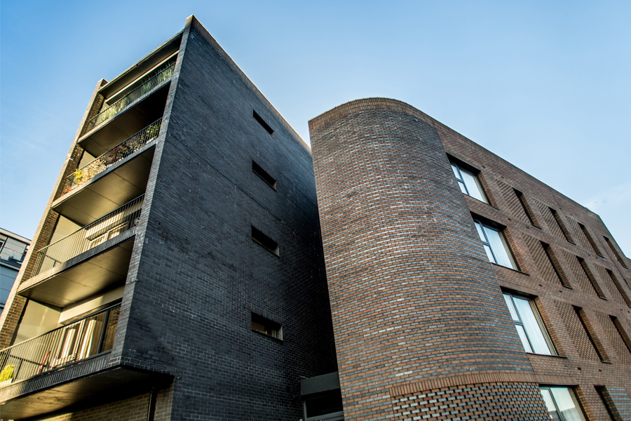 apartment block with glass balconies, residential development, curved brick wall, cotton field park