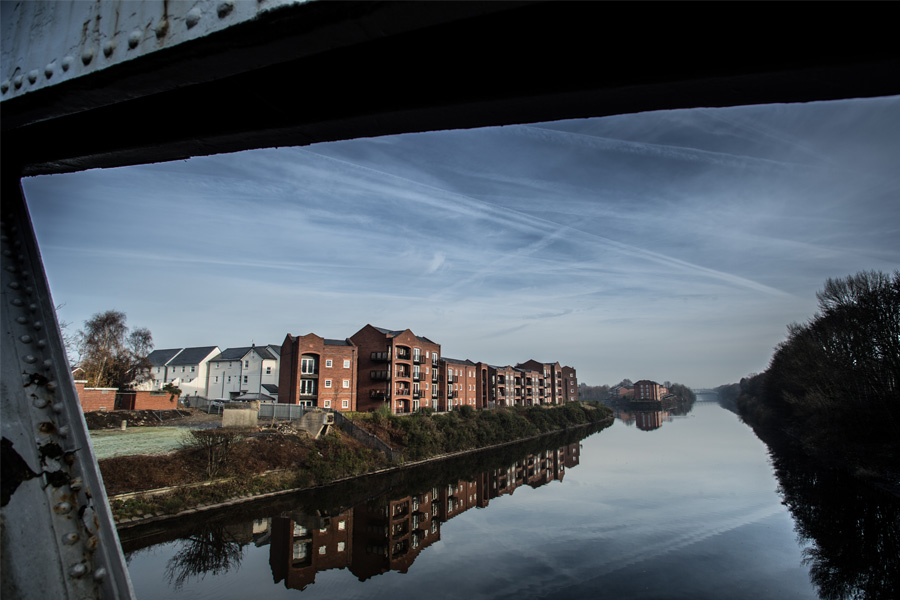 view of walton locks residential development through iron canal bridge, manchester ship canal