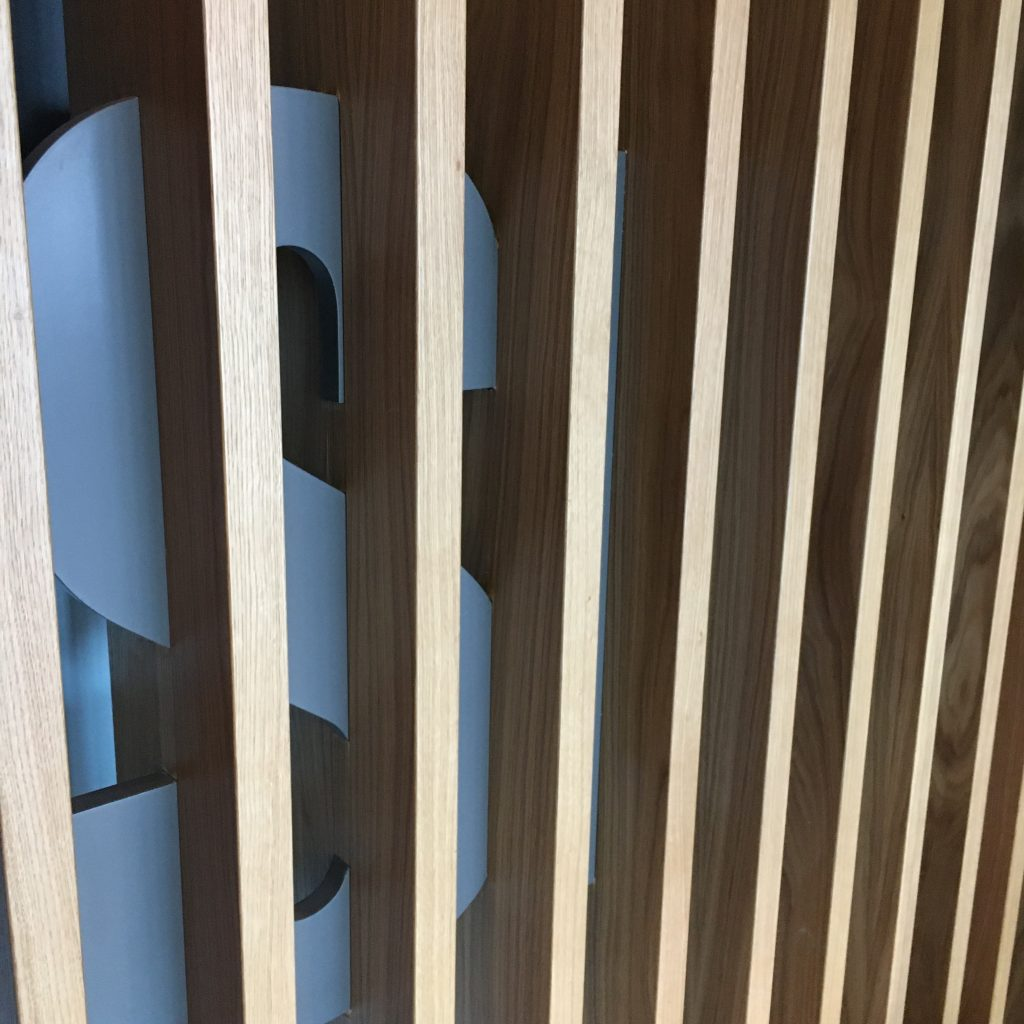 Slatted timber screen with company logo signage