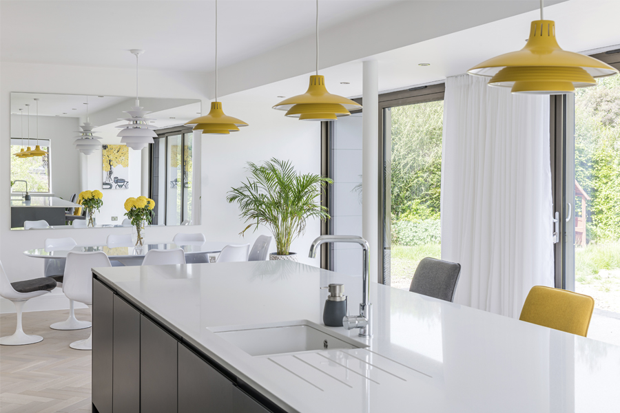 kitchen island with yellow pendants and tulip dining set