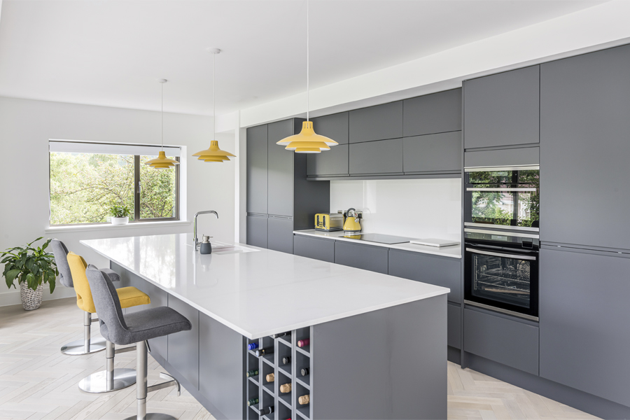 matt grey open plan kitchen with living wall and island with wine rack and quartz top,