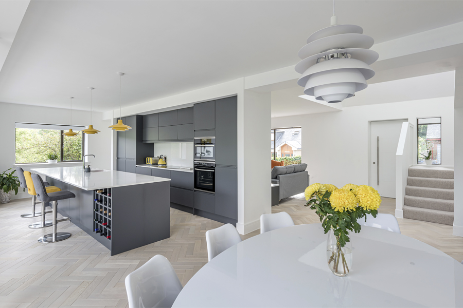 view through open plan kitchen, dining and livings areas, showing kitchen island and living wall,