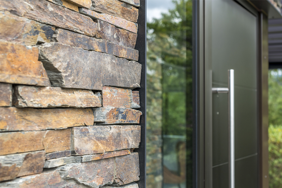 detail of new front door, with pull handle, side glazing and layered stone panelling
