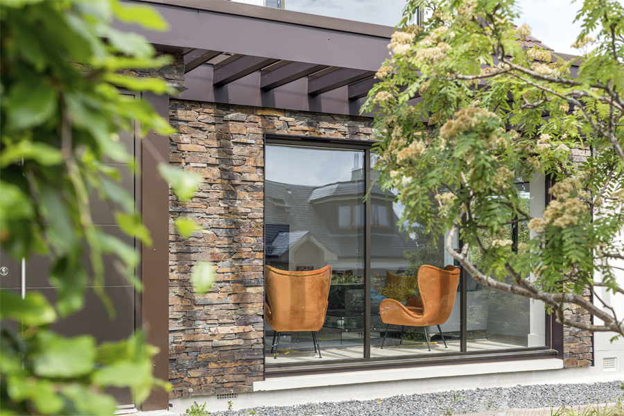 view of refurbished bungalow in peebles taken through the trees showing picture window, modern pergola and stone panels