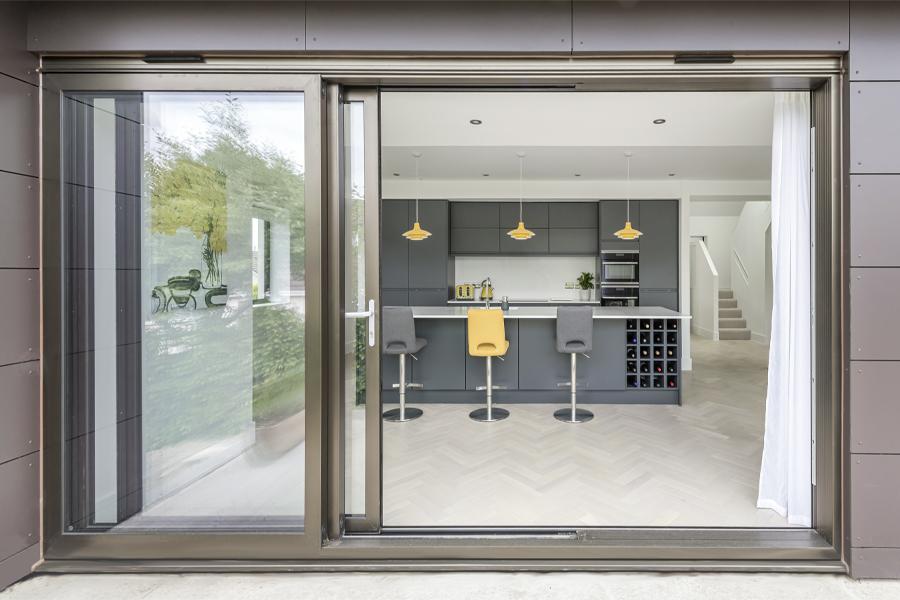 sliding patio doors opening from garden terrace into open plan kitchen diningroom