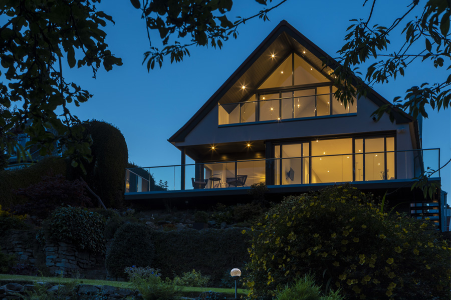 dusk elevation photo of a 2-storey rear extension to a 1930's bungalow in edinburgh with large glazed screens and sliding doors
