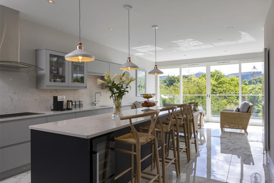 kitchen island in open plan kitchen opening onto terrace through sliding glass doors, edinburgh kitchens, kitchen design,